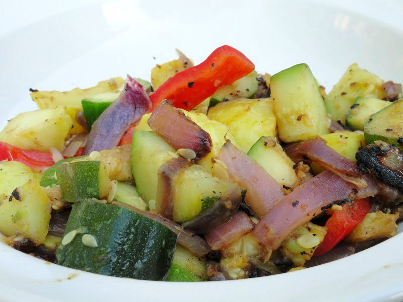 Zucchini, Summer Squash, Red Bell Pepper with Ginger and Garlic cooked and served in a white bowl.