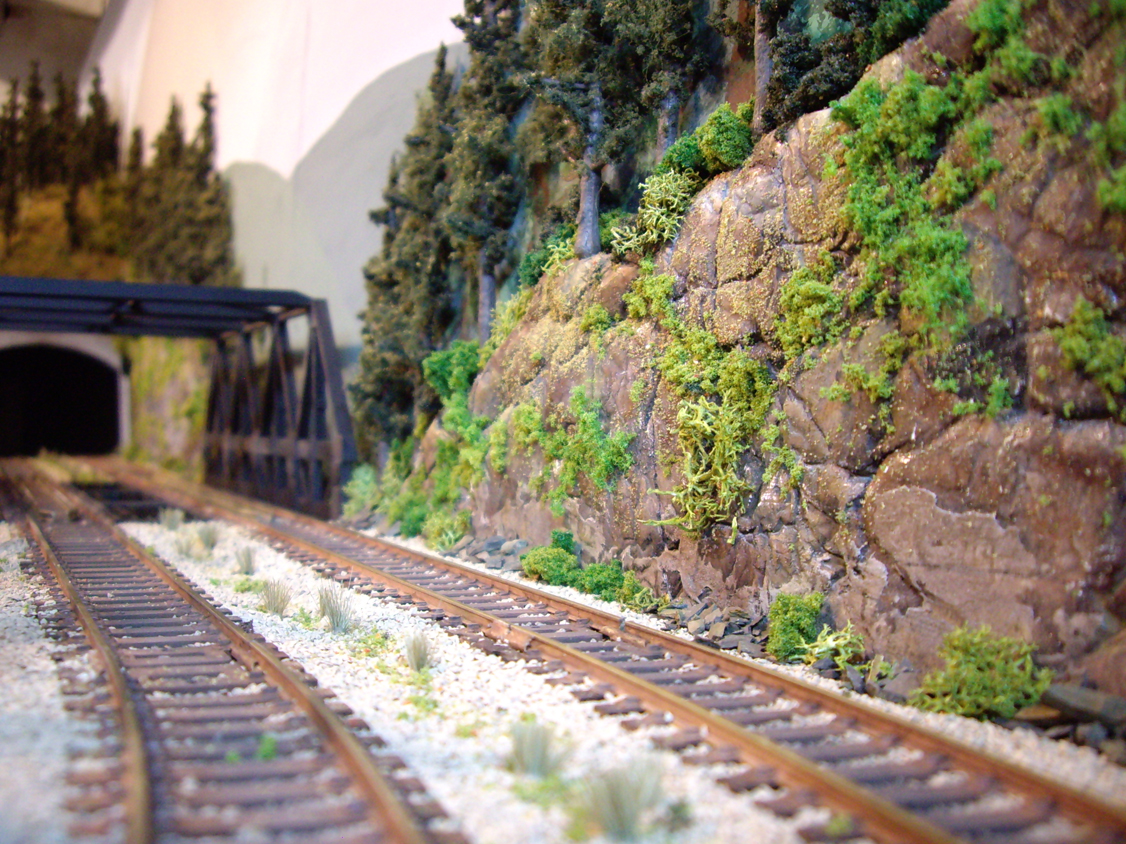 Ballasted track and completed scenery on plaster rock outcroppings leading to upgraded warren-truss bridge