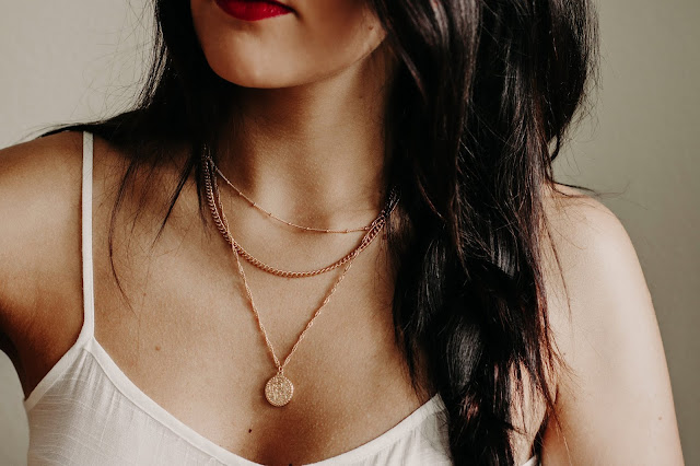 a women wearing a layered gold necklace