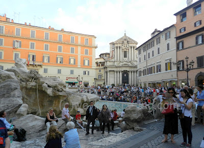 There is a large crowd in the small space in front of Trevi Fountain