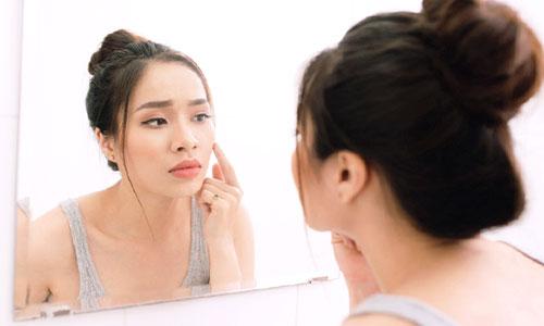 chica preocupada mirándose al espejo