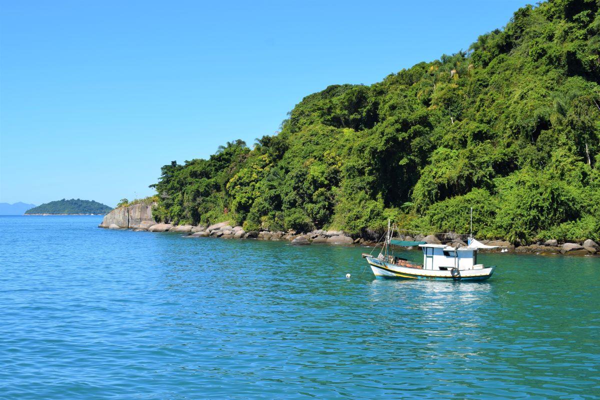 escuna pequena em frente a uma pequena ilha no oceano