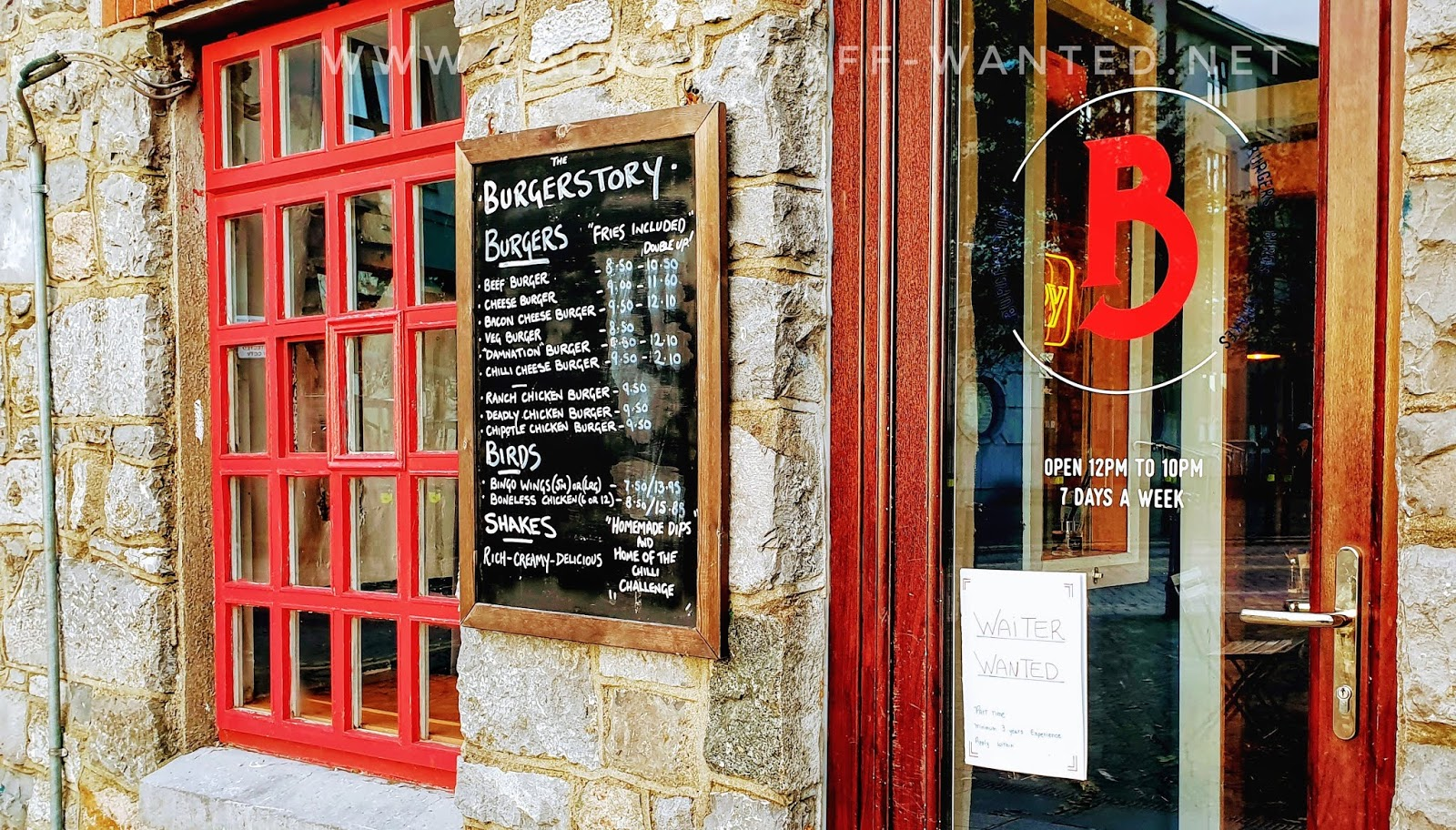 front door with job advert, and window with small panes of glass in red wooden frames.   Plus the Burgerstory menu on a blackboard.