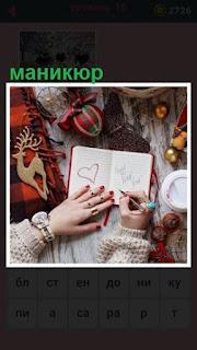 женщина рисует в блокноте с маникюром на пальцах