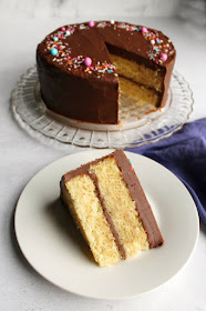 french butter cake with old fashioned fudge frosting and sprinkles in background with one slice served in foreground