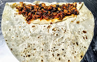 Placed chicken fillings on a rumali roti for chicken kathi roll