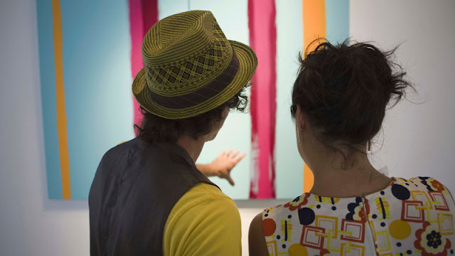 man and woman looking at artwork