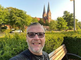 Ich sitze am Neuruppiner See und habe die Kirche im Hintergrund