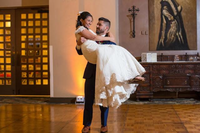 groom holds bride smilling