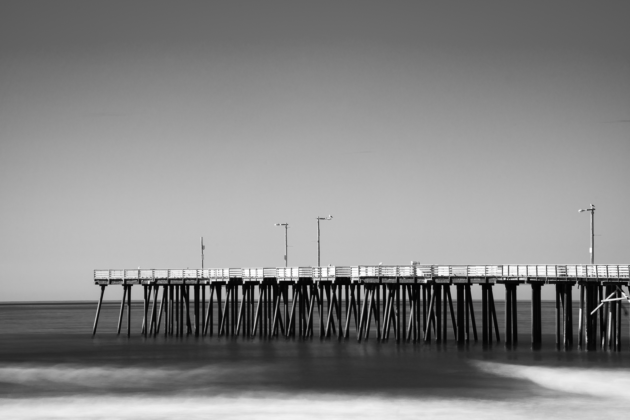 a black and white photo of the pier at pismo beach california