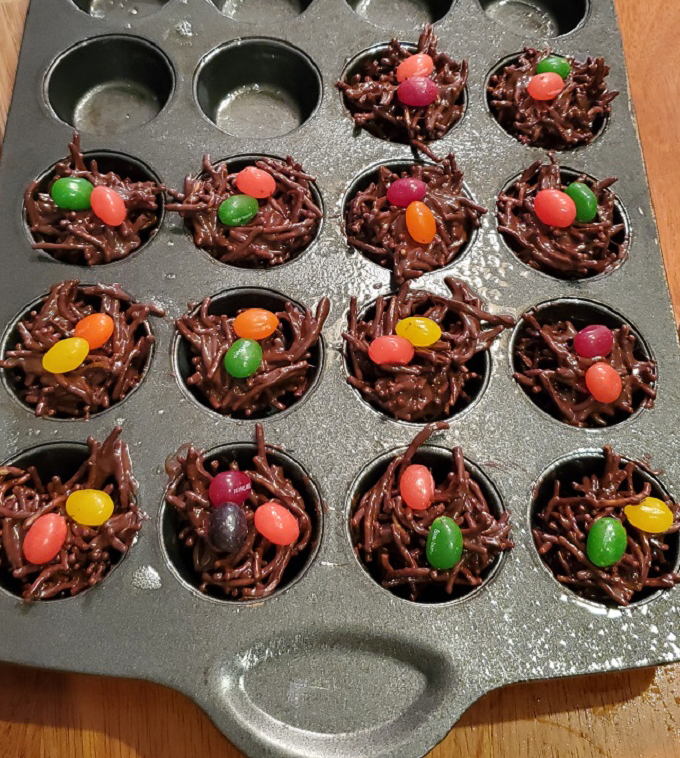 these are nests made out of melted chocolate, Asian fried noodles and topped with jelly beans in a mini muffin pan