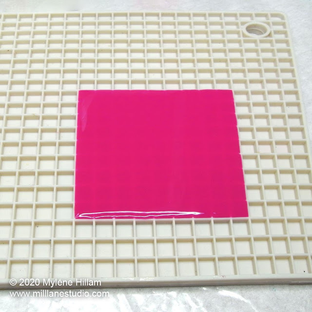 Bright pink resin poured in the shape of a square on a pixel trivet