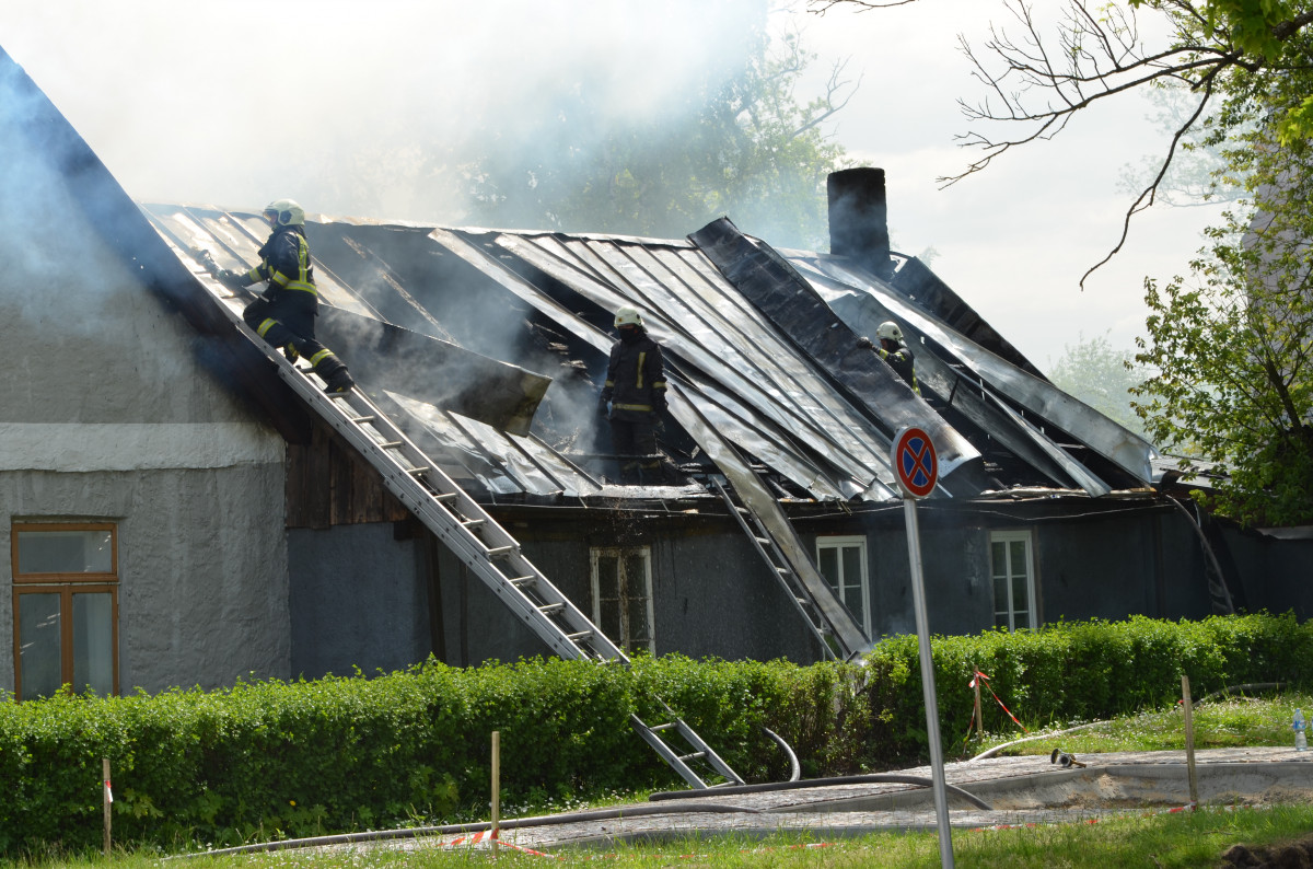 Ugunsdzēsēji caur caurumiem jumtā dzēš liesmu avotu