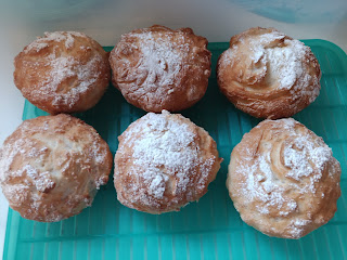 Six cooked bread rolls, brown and crispy on top and lightly floured.