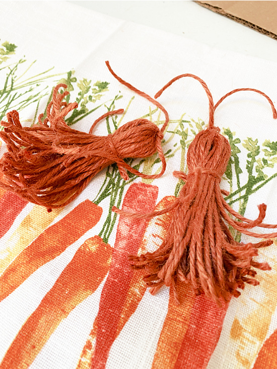 2 orange tassels on the carrot tea towel