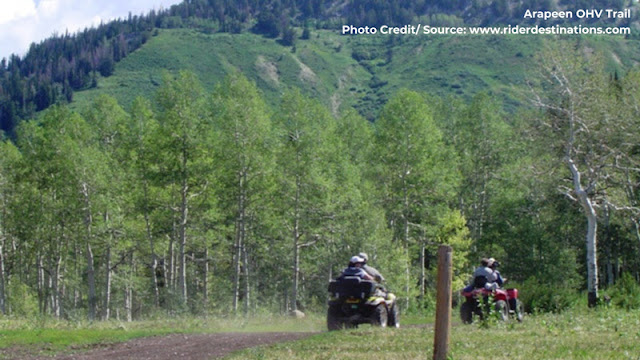 two ATV's riding a trail through lush green mountains
