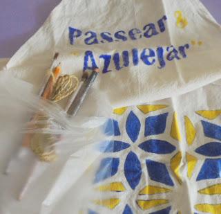 Avental, pinceis e lapis num saco plástico