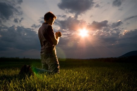 A man kneeling outside in the grass with his hands fold in front of him praying