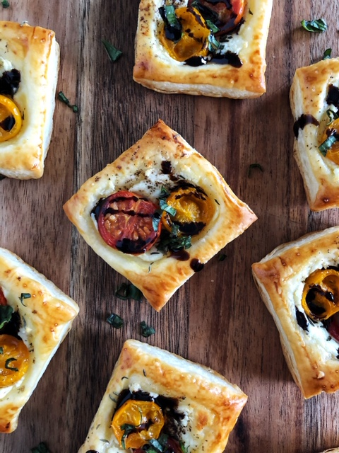 puff pastry with goat cheese, roasted tomatoes, herbs and balsamic glaze on a wooden board