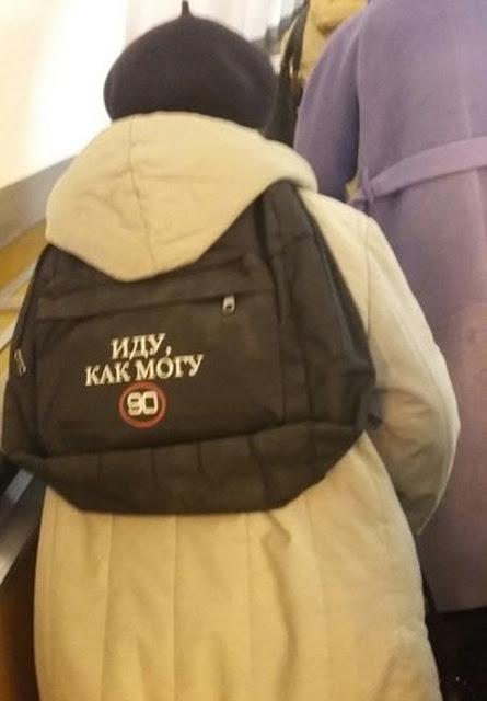 """Esta velha senhora carrega uma mochila na qual ela diz: """"Eu avanço como posso."""" Muito original sim senhor"""