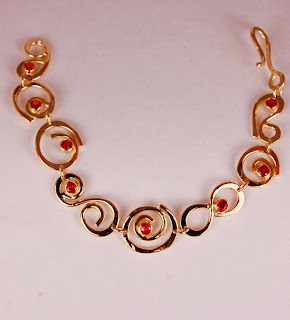 18k yellow gold bracelet with looping wire design and bezel set round orange sapphires