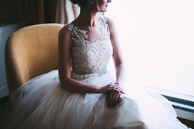 Novia con su vestido sentada y mirando soñadora por una ventana