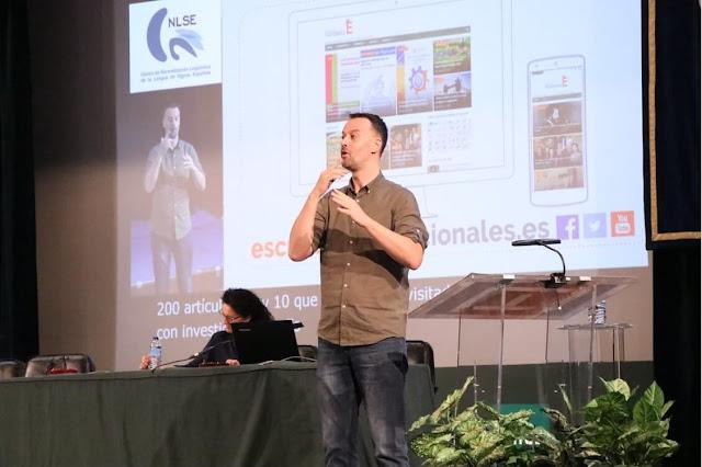 Comunicación presentada en el Congreso CNLSE por Emilio Ferreiro, de pie con camisa marrón y pantalón vaquero, fondo de la presentación con una imagen de la web de Escuelas Excepcionales