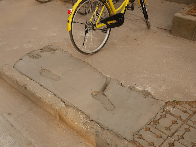 footprints and bicycle tire mark in wet concrete