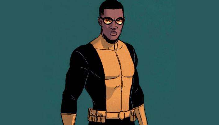 Homem negro de cabelos pretos curtos e raspados dos lados. Ele usa óculos escuros amarelos e está sério olhando para a frente. Ele veste um uniforme amarelo com mangas compridas pretas e luvas amarelas, além de um cinto amarelo com bolsos presos. A parte visível de sua calça é preta.