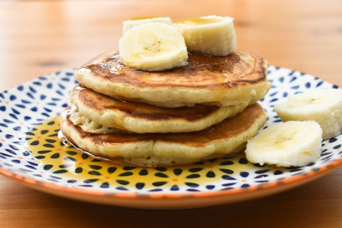 A small stack of banana pancakes drizzled with maple syrup