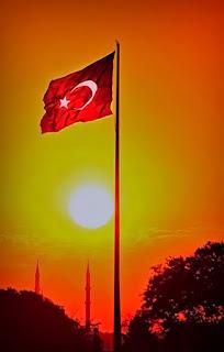 Sancak, güneş batarken dalgalanan Türk Bayrağı ve uzaktaki minareler