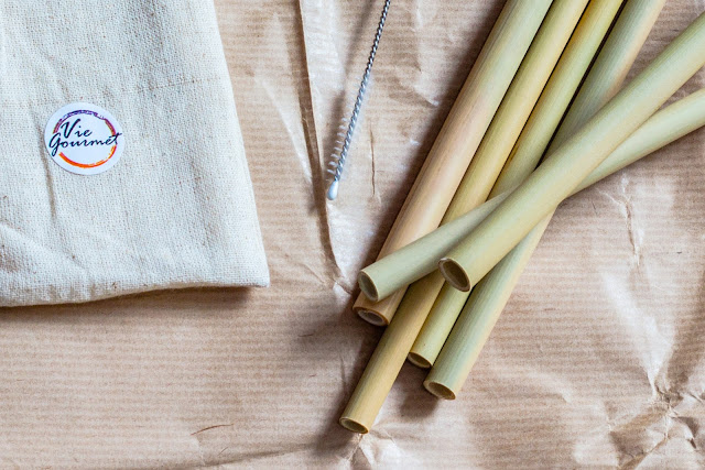 A fabric pouch, cleaning brush and pile of 6 bamboo straws of varying diameter