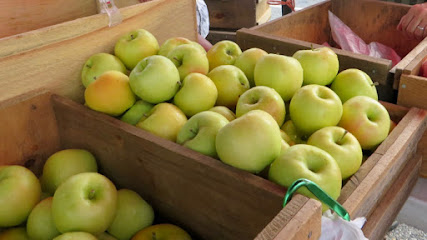 Yellow apples, some faintly blushed, in a wooden bin
