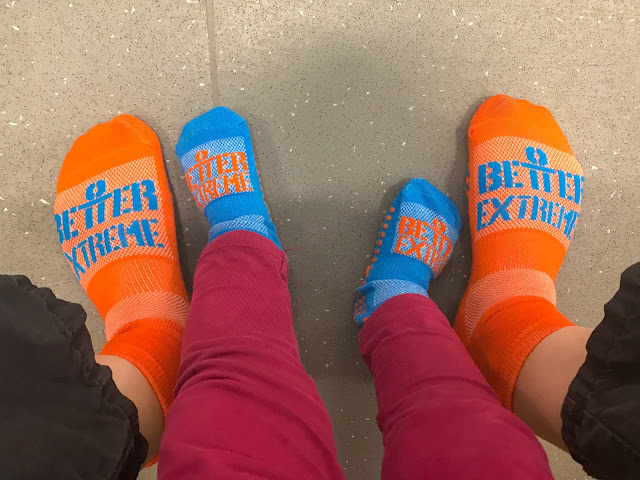 A photograph of adult feet in Orange Better Extreme socks either side of Toddler feet in Blue Better Extreme Socks