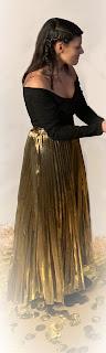 tenue composée d'un haut noir aux épaules dénudées et d'une jupe longue dorée