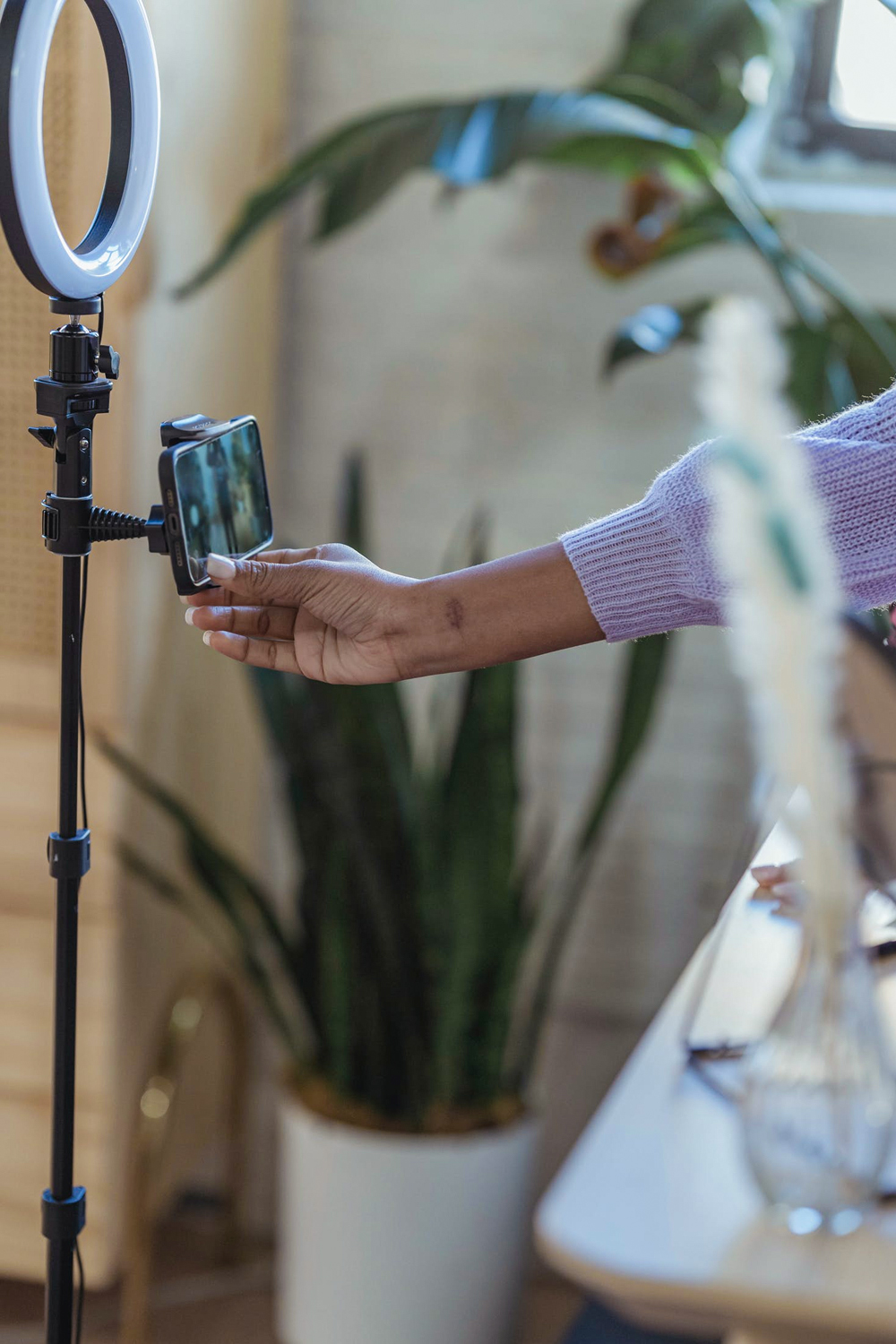 Woman using smartphone on tripod with ring lamp
