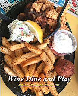 The seafood combo plate with blackened grouper, fried clam strips, french fries, hushpuppies and dipping sauces at the Olde Fish House Marina restaurant in Matlacha, Florida