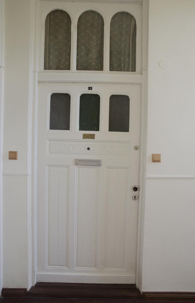 białe odmalowane drzwi w kamienicy
