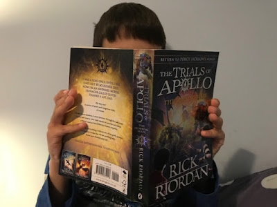 Child reading a Rick Riordan Trials of Apollo book