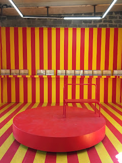 A gallery room with yellow and red stripes with a carousel in the middle and a series of photographs depicting pieces of a column running on the walls