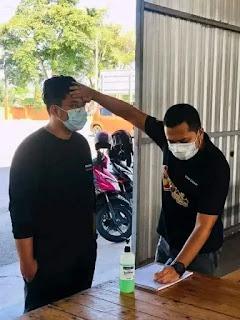 Hombre con mascarilla toma la temperatura a otro con la mano en la frente