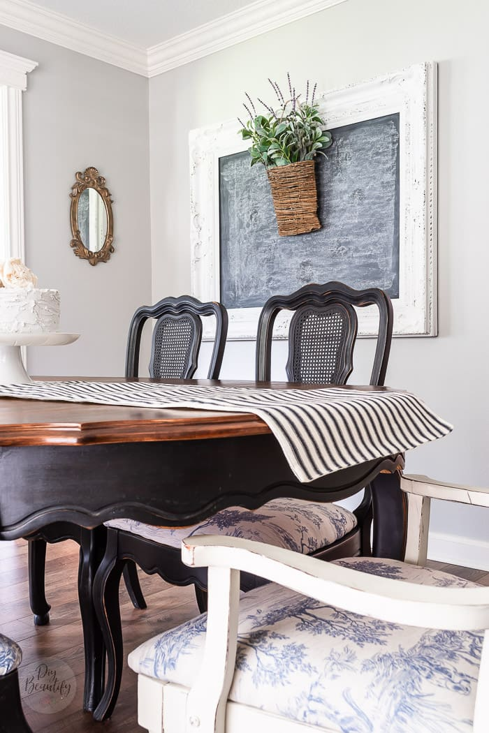 ornate white chalkboard, vintage black dining chairs and striped table runner