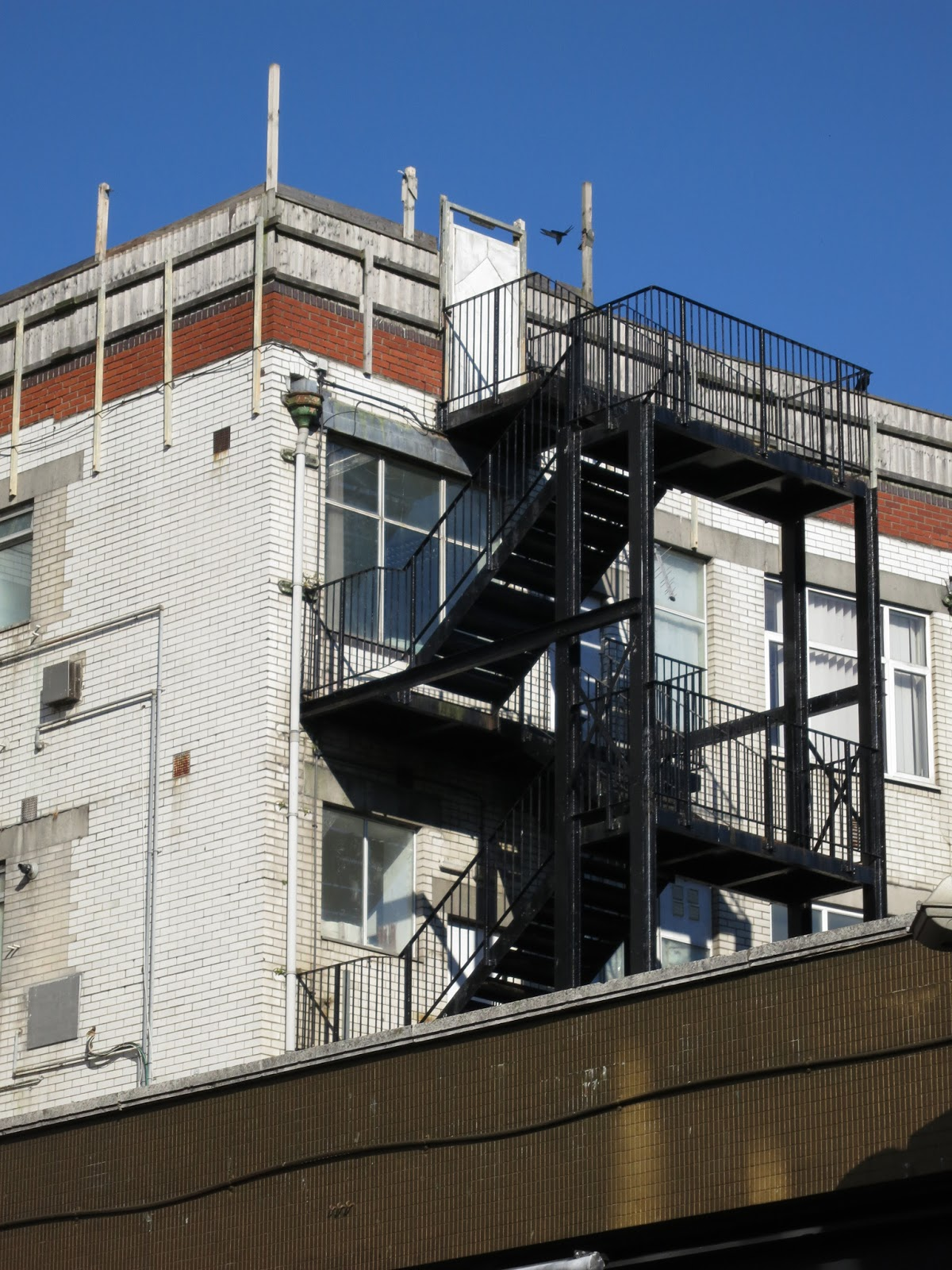 Building with fire escape,whit bricks and windows.