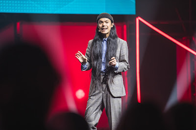 A photo of Ash Chang talking on stage at the event