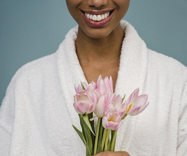 mulher sorrindo vestida com um roupao de microfibra