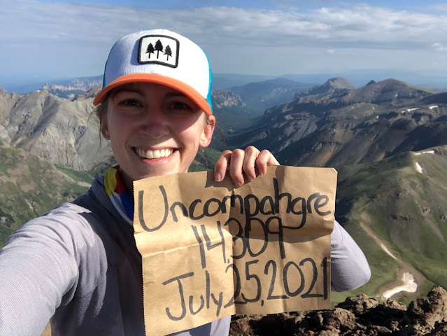 woman on top of a mountain holding a sign with the mountain name