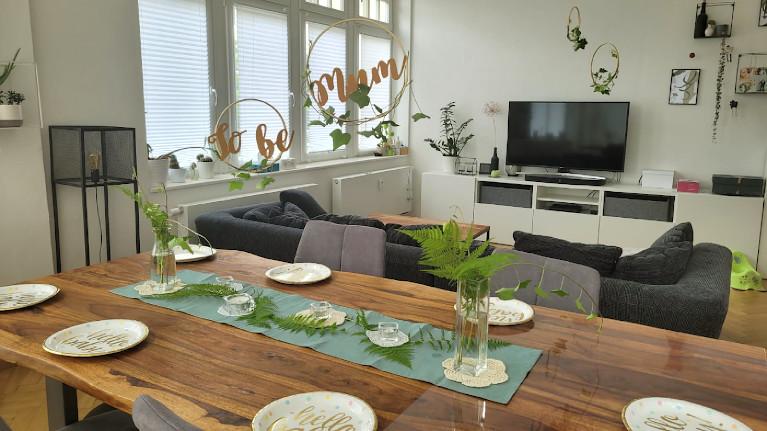 Gedeckter Tisch mit grüner Dekoration zur Babyparty