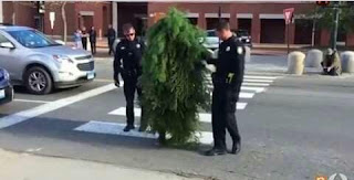 Hombre vestido de arbusto acompañado de la policía