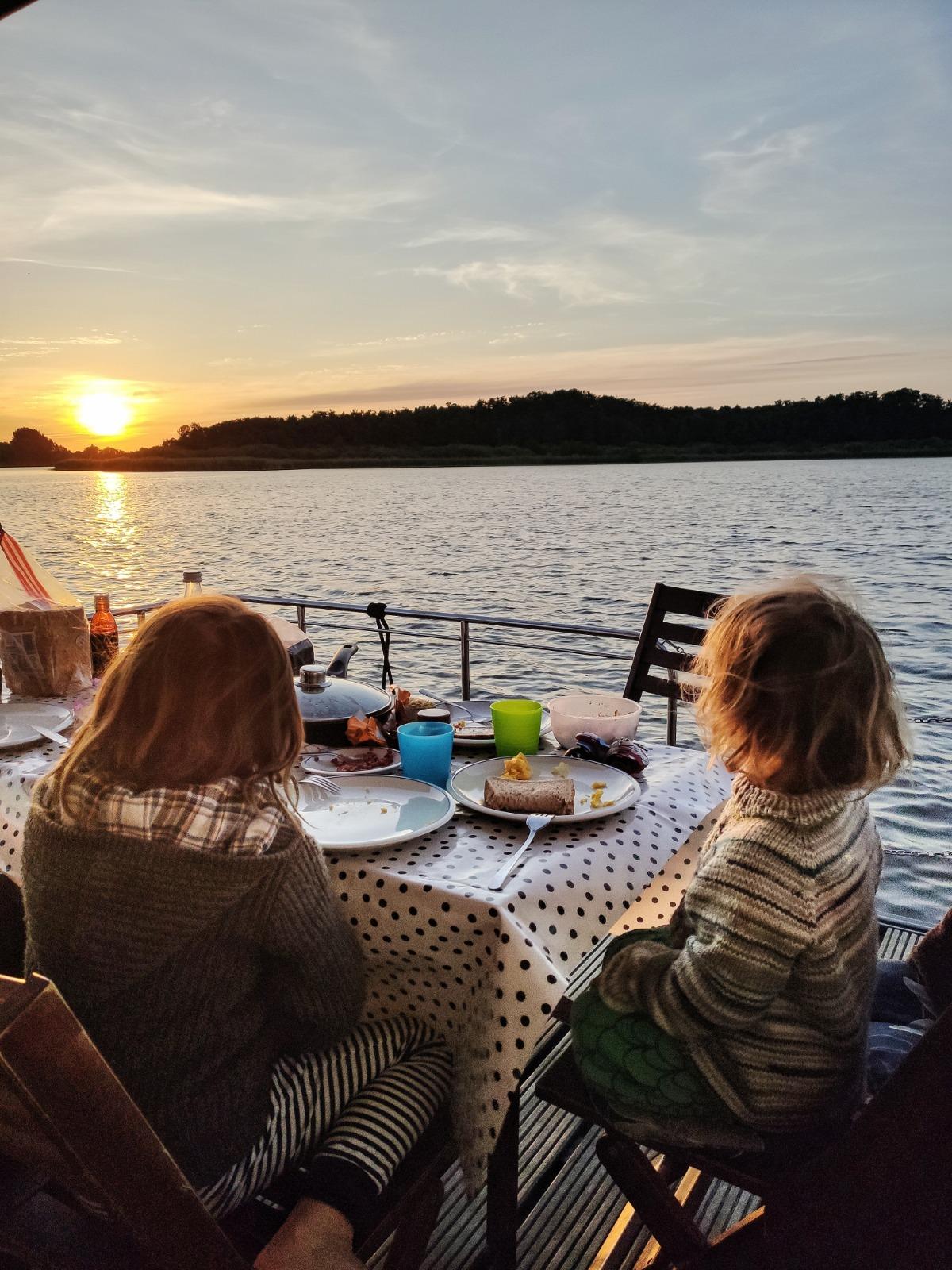 Mit Kindern den Sonnenuntergang vom Hausboot genießen