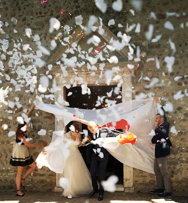 Pareja de novios saliendo de la ceremonia atravesando una tela que sujetan dos invitados